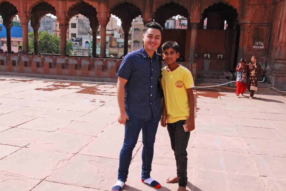 local-kid-asking-tourist-take-picture-jama-masjid-mosque-delhi-india